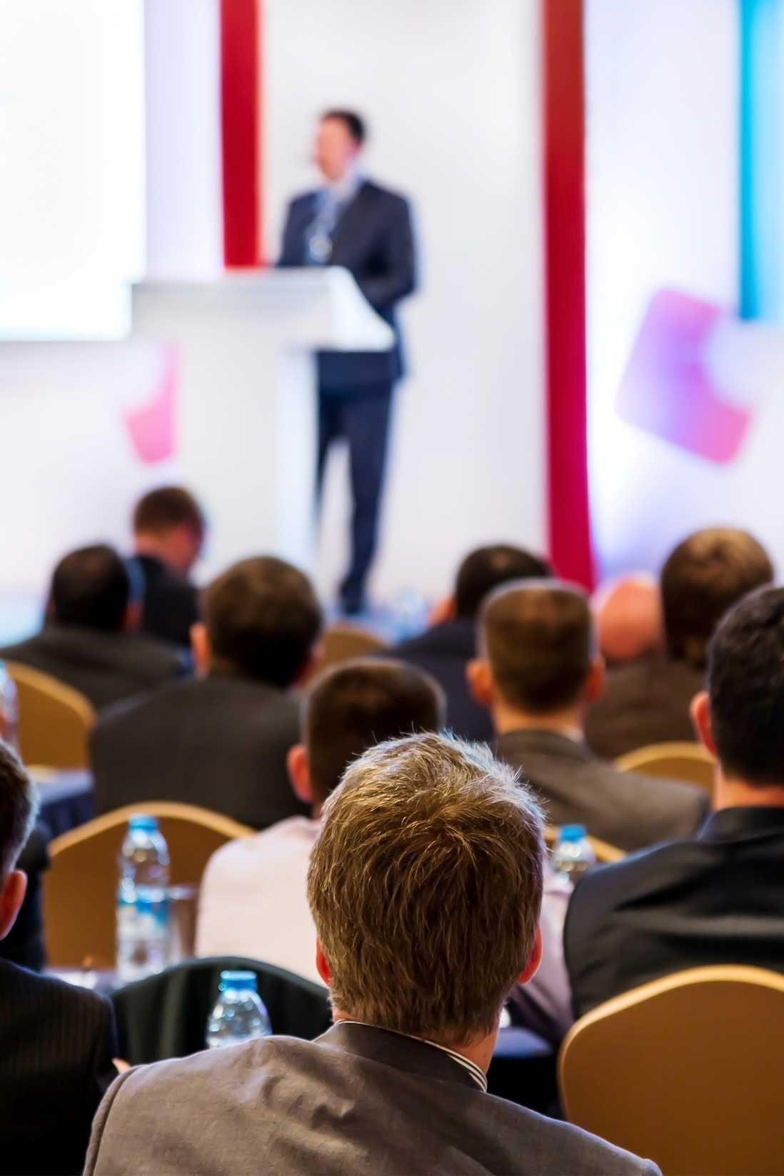 Image of a croud at a conference with speaker blurred in the distance