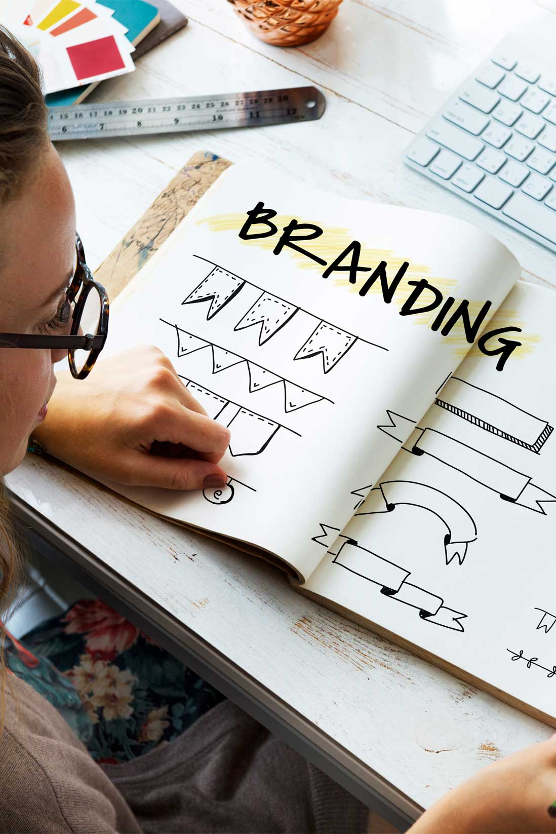 Image of a woman looking a different styles of branding sketches
