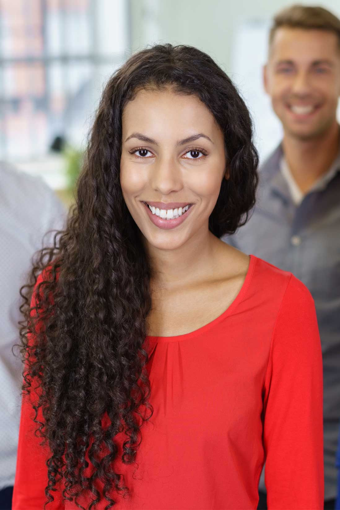 Image of smiling, happy female client with man in the background