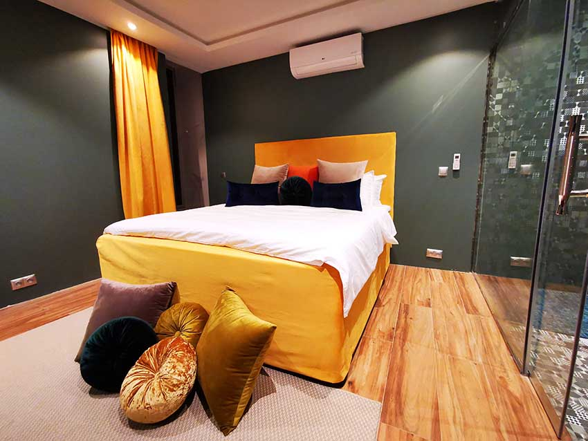 Green bedroom with yellow bed and luxury bathroom