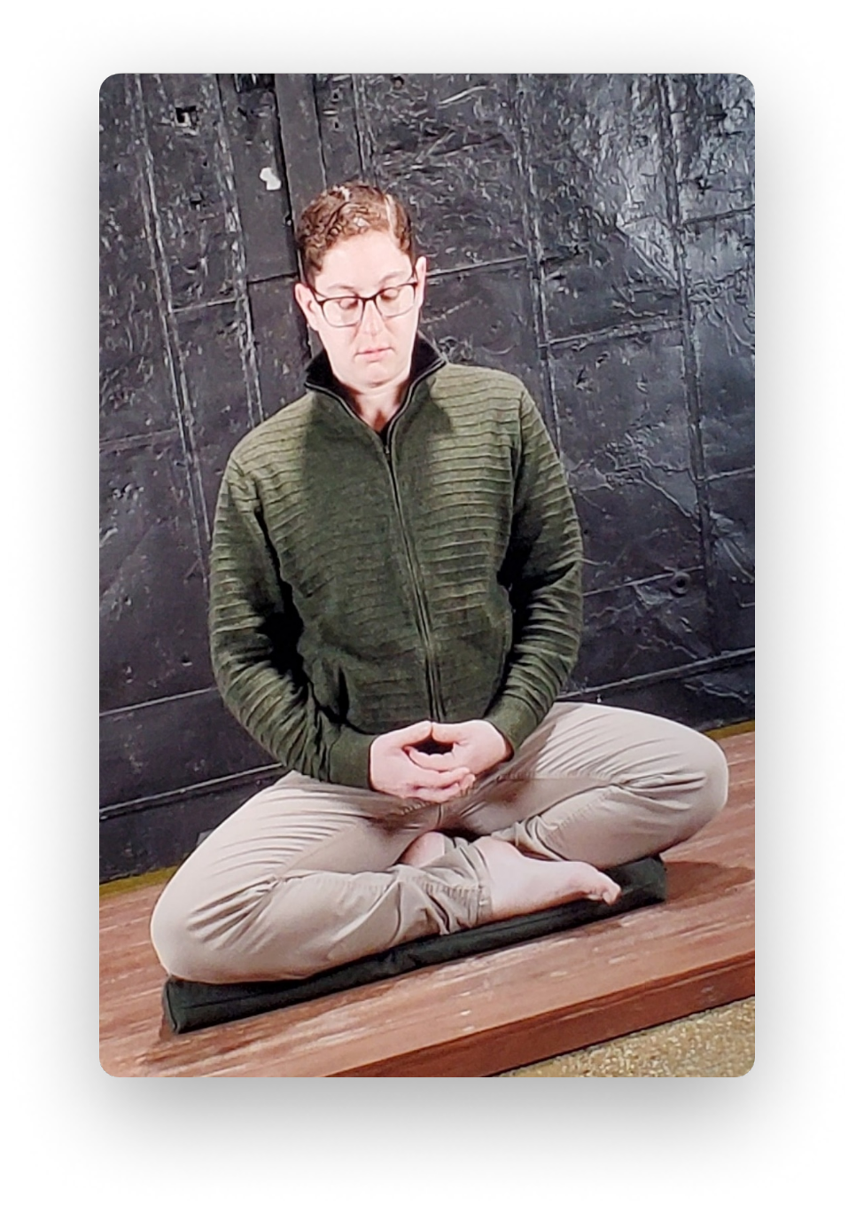Photo of Adam Weinberg meditating in a half lotus position.