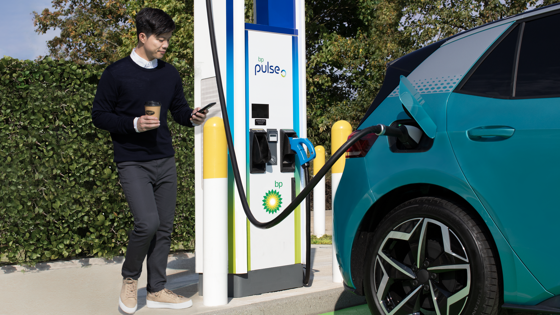 Electric Car Charging a Man looks at the App on his Smart Phone