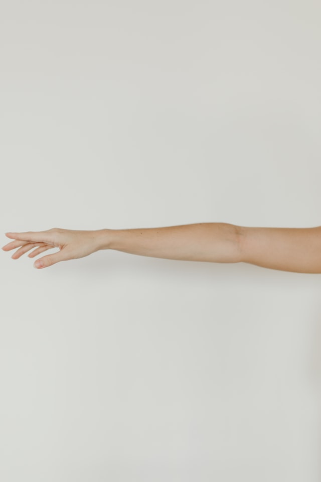 Person extending their arm on a white background