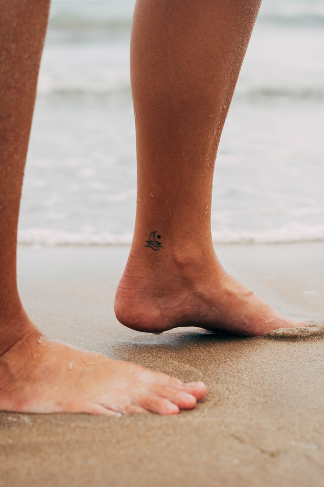 Person's shins standing on a beach