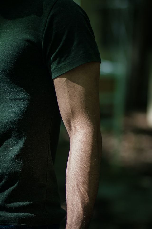 Man wearing green shirt with arm exposed