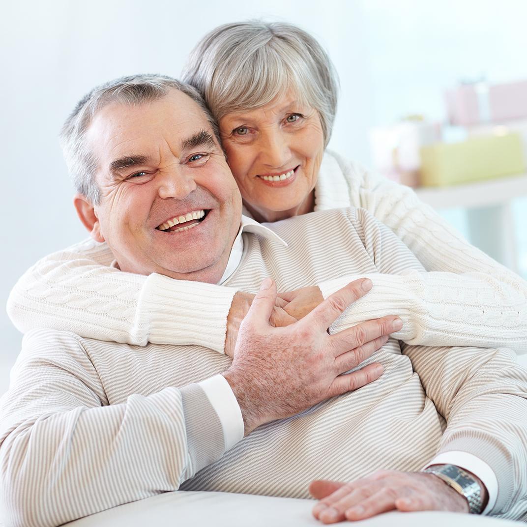 Pareja de abuelitos demostrando bienestar abrazados