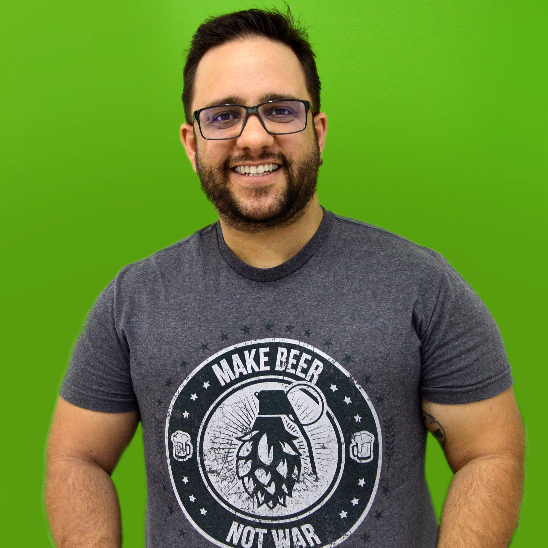 Foto do professor Wyll Bueno sorrindo em um fundo verde