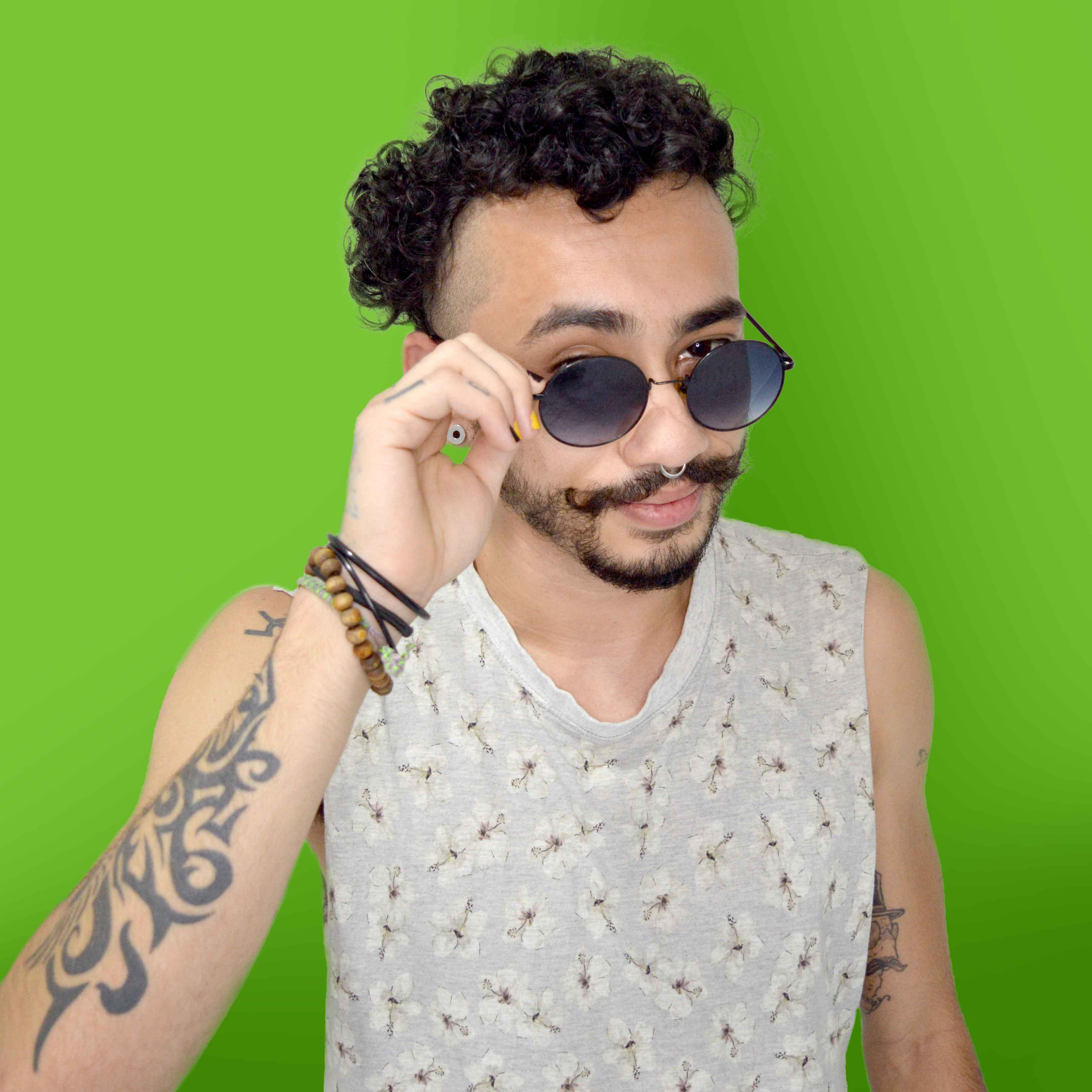 Foto do professor Marc Assis sorrindo em um fundo verde