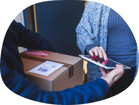 A courier handing a box to a happy woman.
