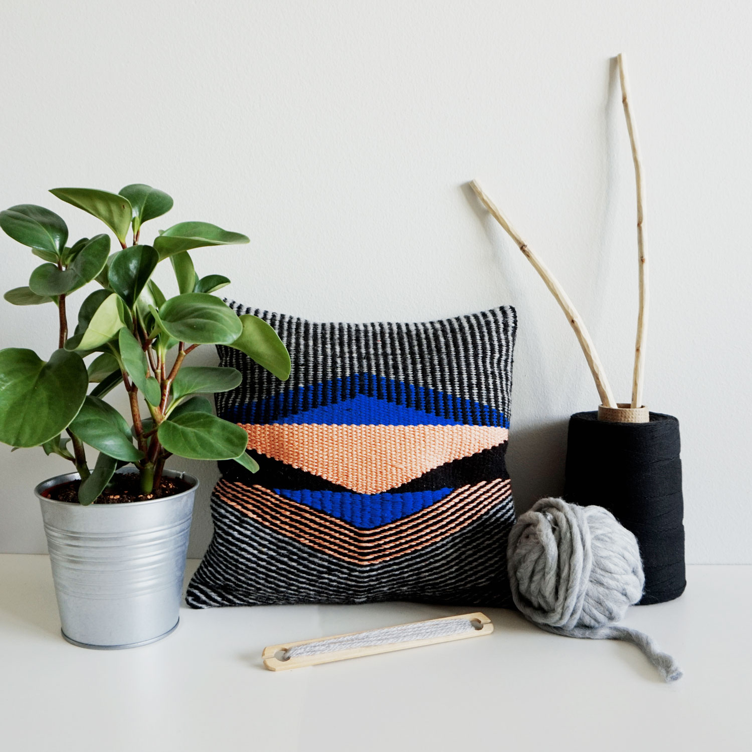 A small geometric pillow case with a smooth texture and an interesting play of stripes and solid shapes.