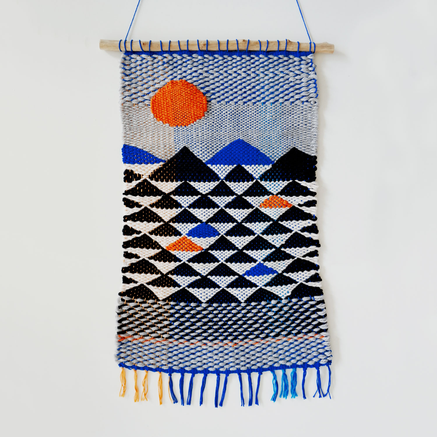 Abstract landscape wall tapestry featuring mountainous landscape and bright orange sun. Short fringe and natural branch hanging system.