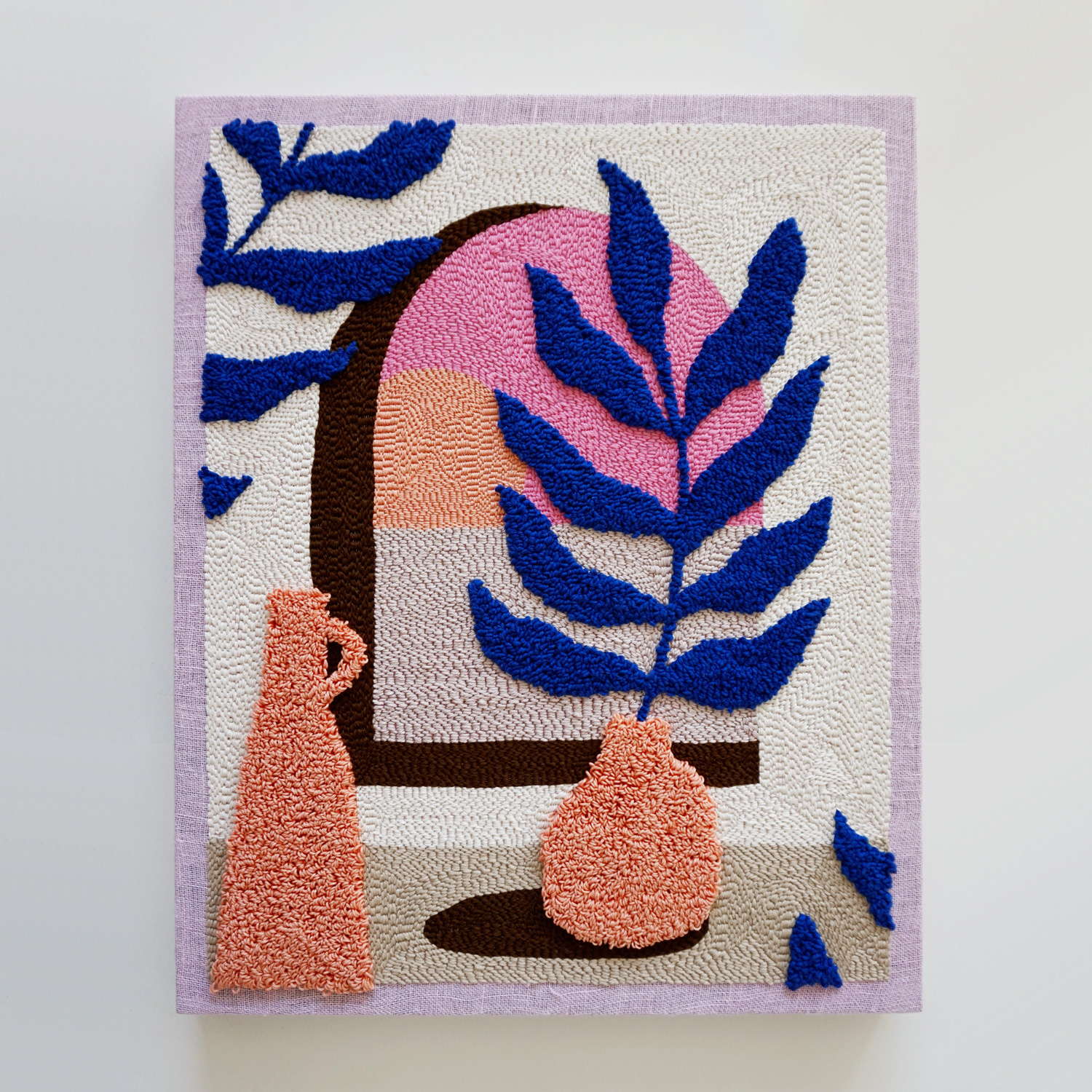 A dreamy and soft punch needle art work, featuring a mediterranean scene looking out into a sunset over the ocean.