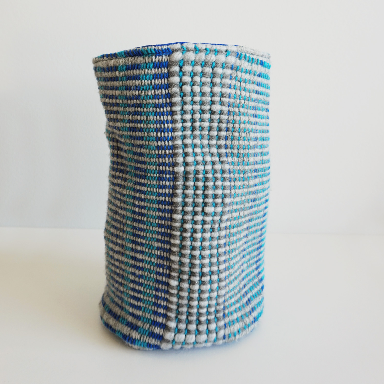 A self-standing soft storage basket with a grey-blue woven texture - perfect for your yarn stash or your collection of woolly socks and house slippers.