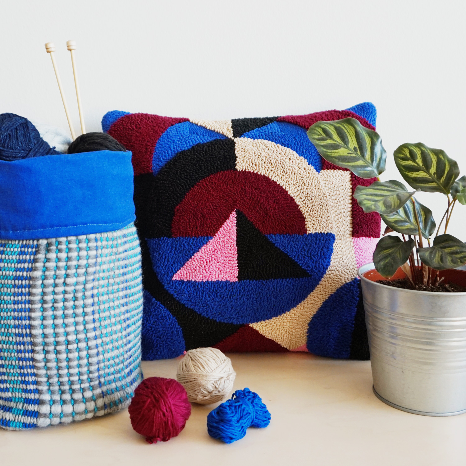 A fluffy punch needle pillow, featuring abstract shapes and a dual-texture with some carpety and some flat parts.