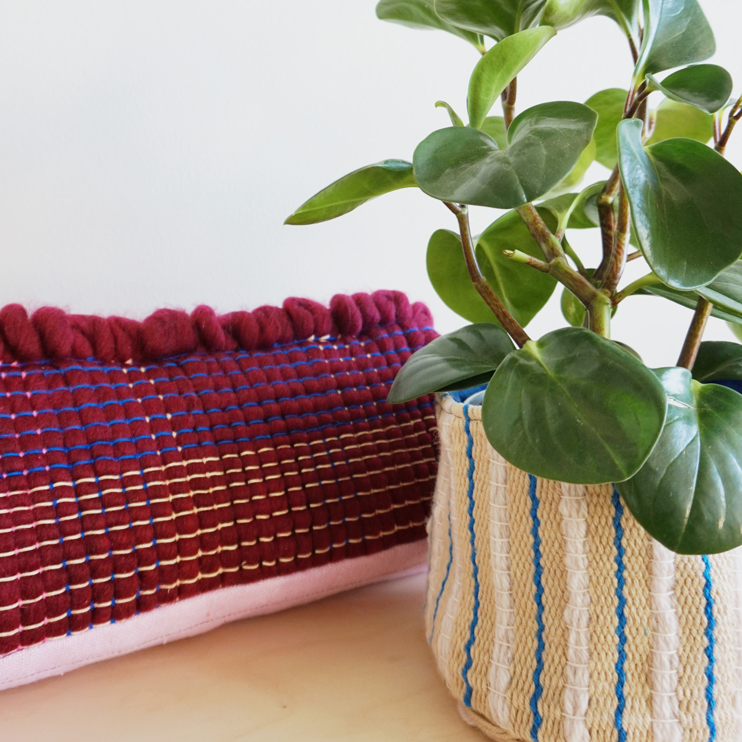 A fun cylindrical pillow with a chunky, burgundy woven section, combined with a subtly striped blush linen base. Comes with a removable inner scrap-pillow.