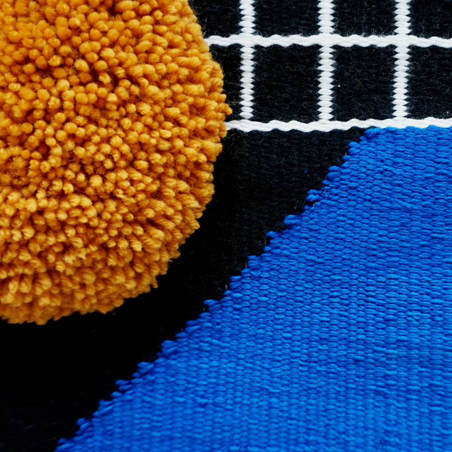 A bold geometric statement piece, featuring a black and white grid, intersected with a bright cobalt blue triangle and a fluffy mustard circle.