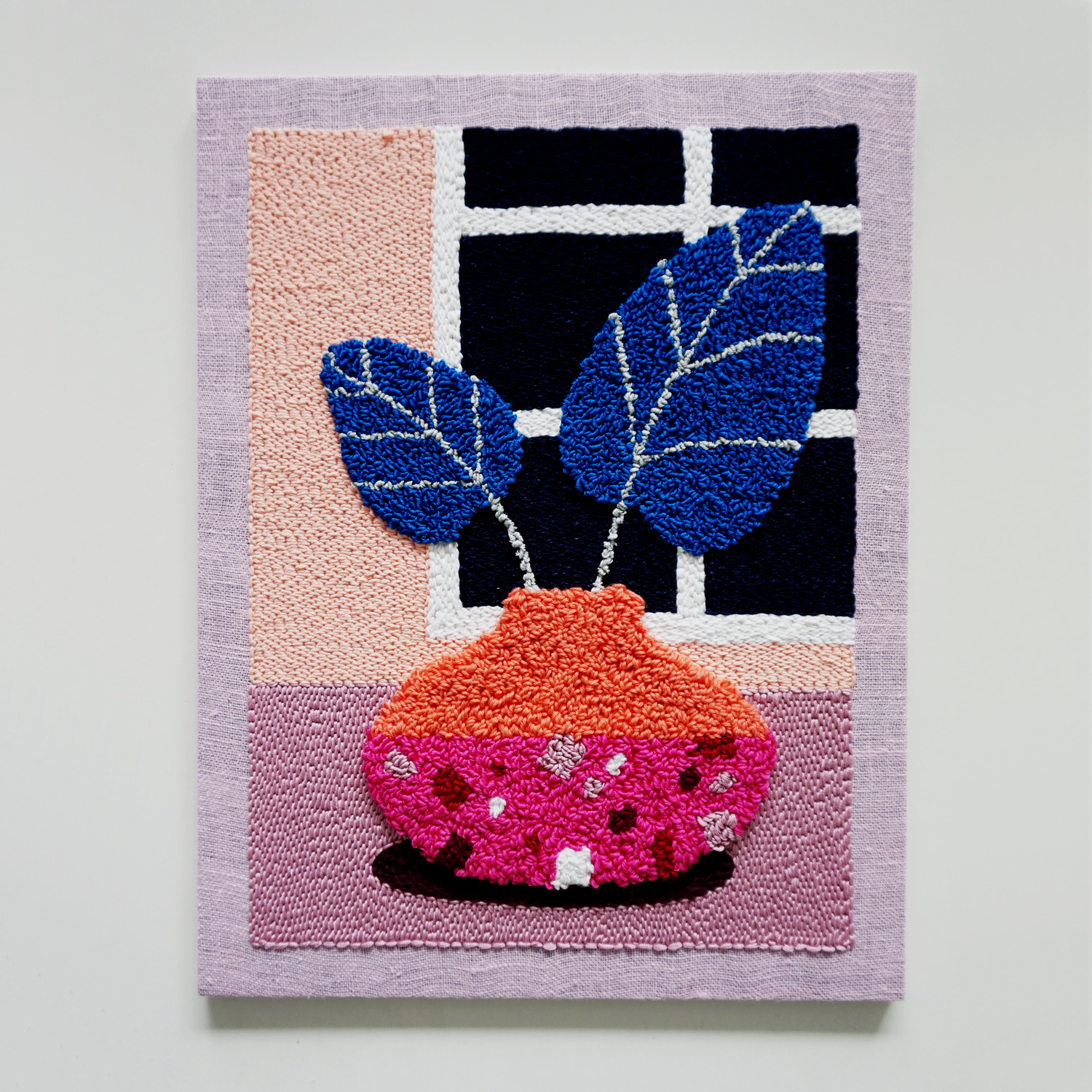 A small punch needle art work, featuring a bold terracotta vase with large blue plant leaves in front of a window overlooking the night sky.