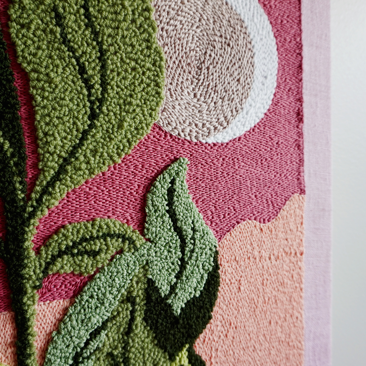 An extra large soft botanical punch needle art piece, featuring a luscious green leafy plant in front of a desert scene.