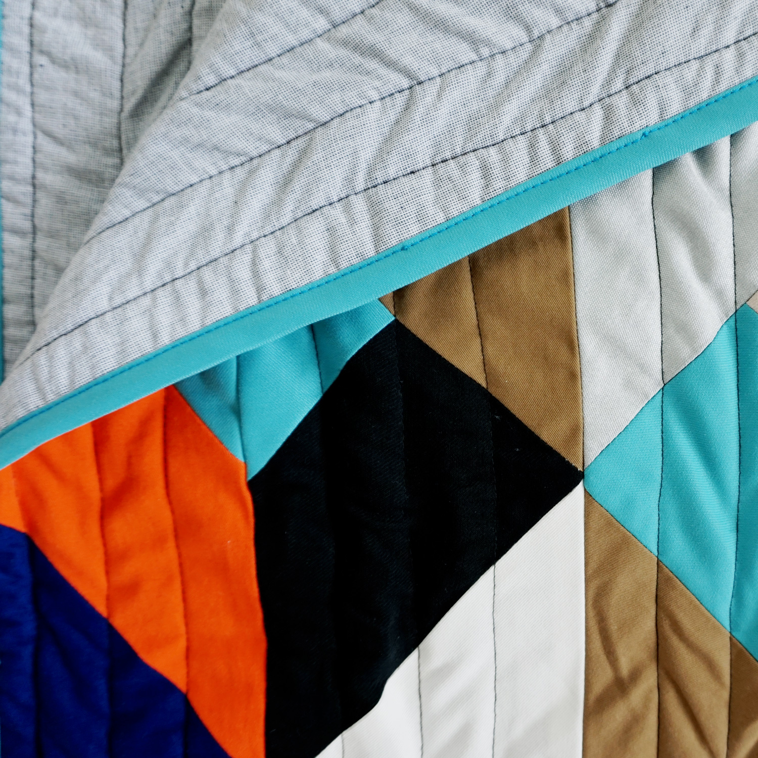 A bold geometric quilt, featuring an architectural pattern of 3D cubes with accent colours of cobalt blue, turquoise and bright orange.