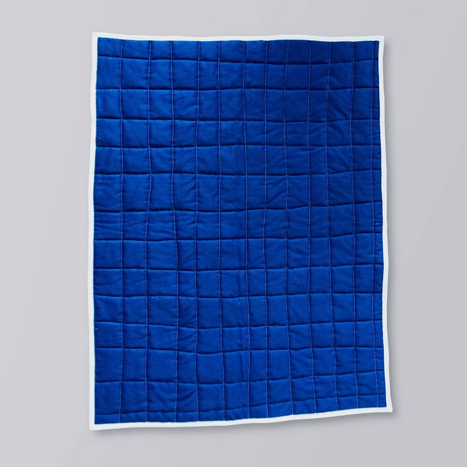 A bright and colorful quilted baby play mat with a pixeled design, featuring accents of blue, pink and orange.