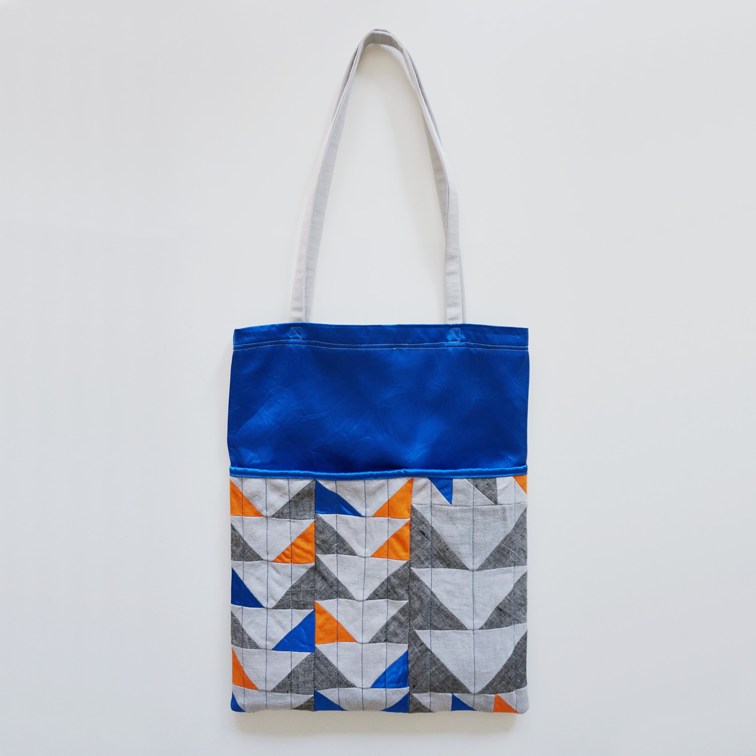 A luxurious (reversible) tote bag with a large quilted pocket, a shiny blue exterior and a silky black lining.