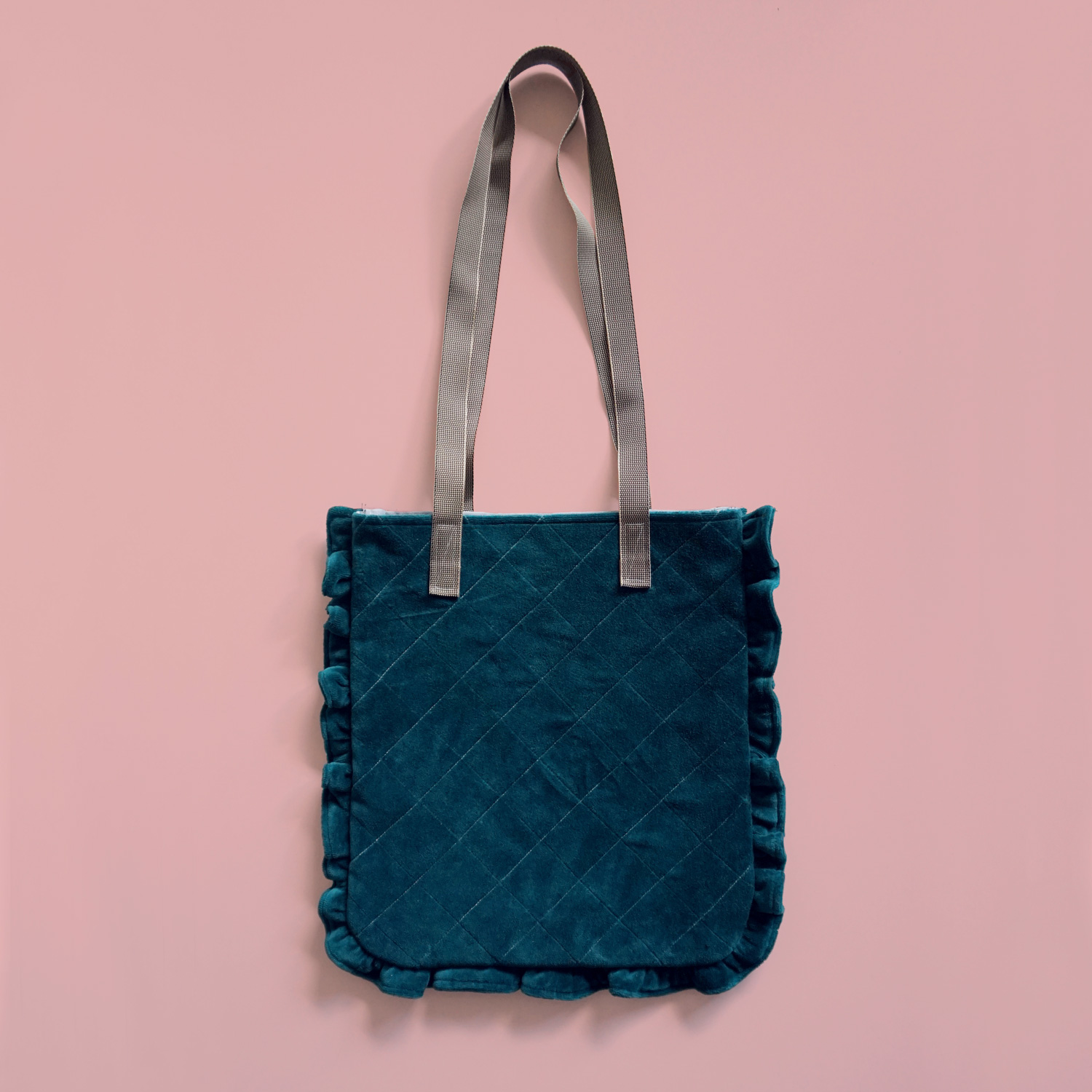 A luxurious and playful tote bag with a ruffled border and quilted outer. A fun statement bag that holds all your day-to-day essentials.
