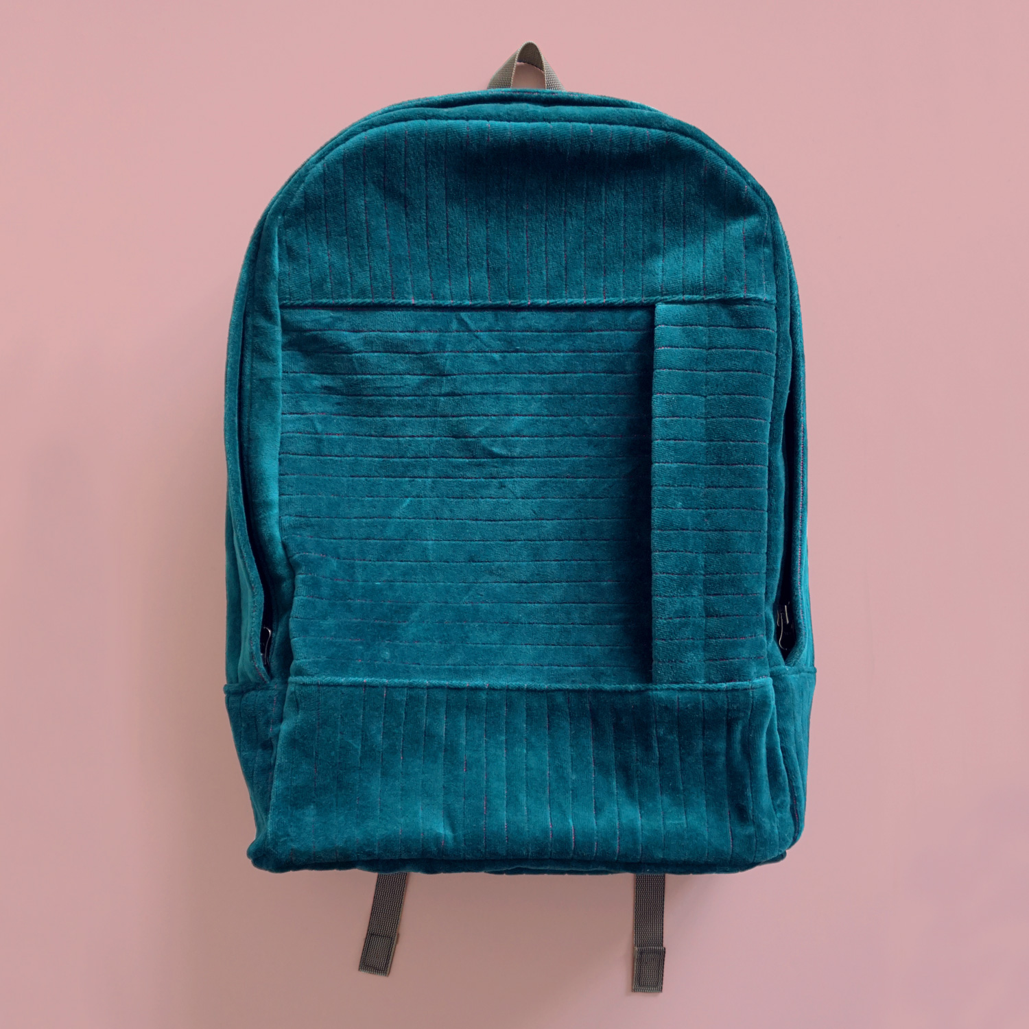 """A velvety and sturdy backpack with neon pink quilted accents. Complete with a padded pocket for a 15"""" laptop."""