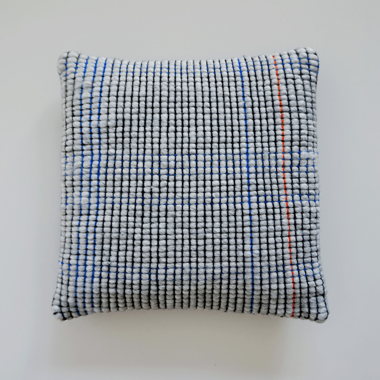 A fluffy and minimalistic pillow with a light grey grid texture. Subtle accents of orange and blue make this pillow a great basic.