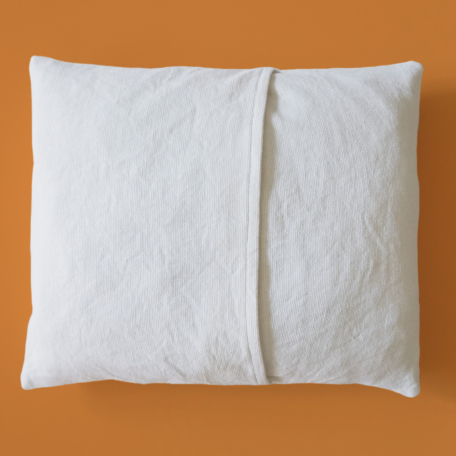 A refreshing orange pillow, that combines quilting, fabric painting and punch needle for a range of subtle textures.