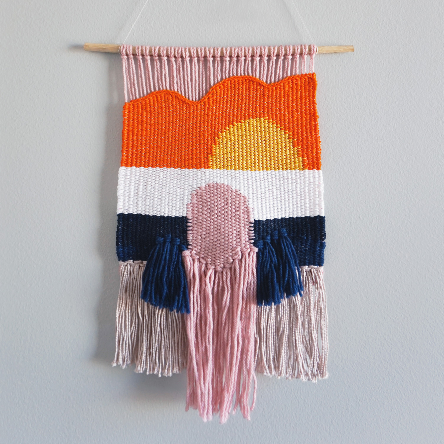A warm and summery wall hanging, featuring a sunset, arch and waterfall. Complete with free form edge and natural branch hanging.