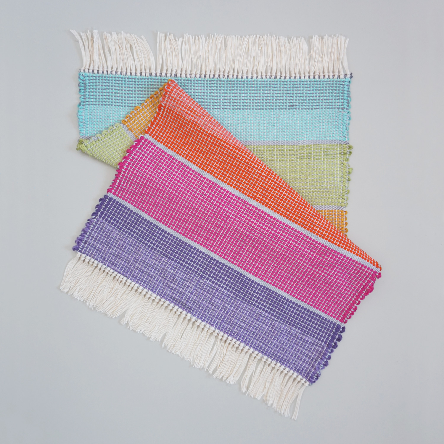 A soft and light multi-colored rug with stripes in pastel rainbow colors. Perfect also as a small table runner.