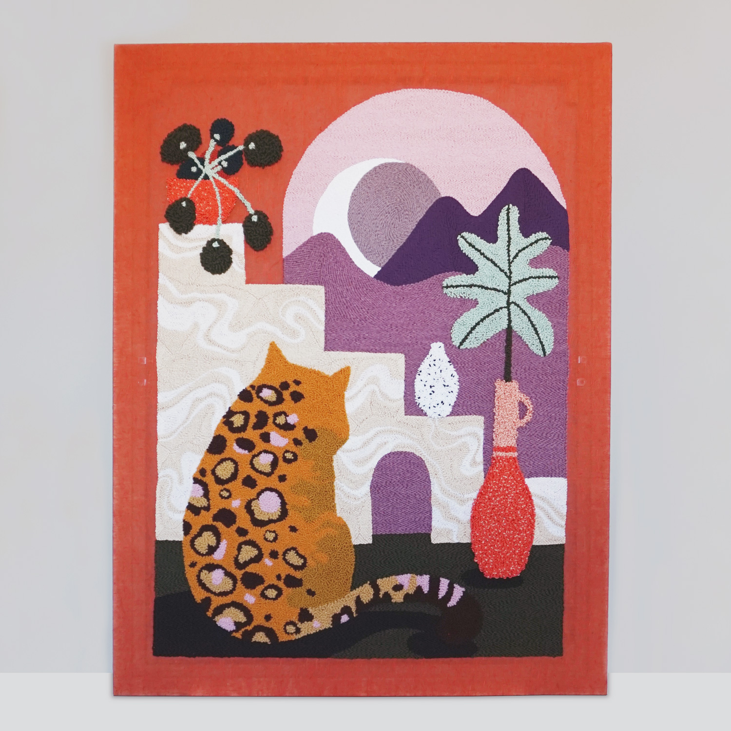 A large punch needle wall art, featuring a fluffy leopard looking out at a desert scene in moon light.