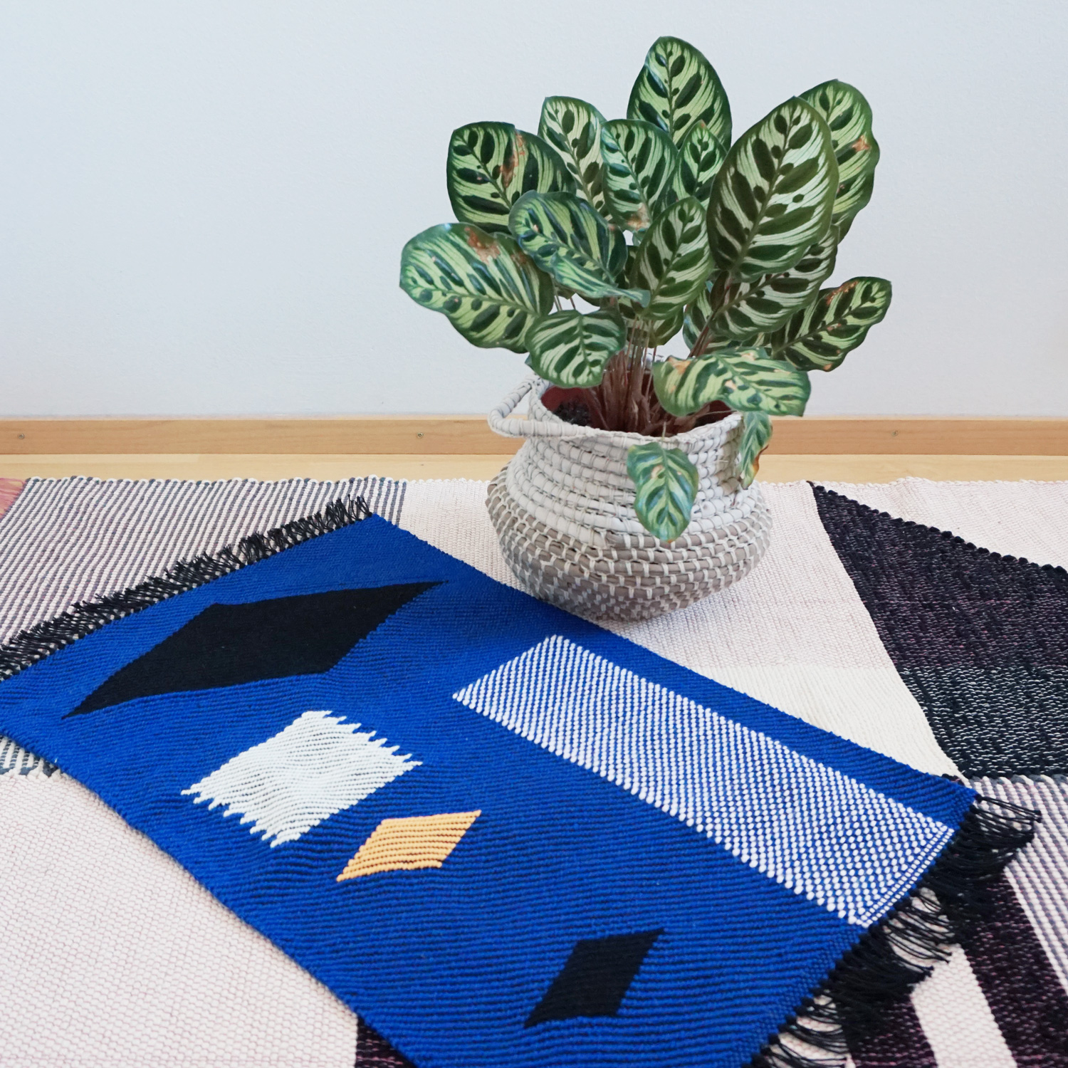 A bright cobalt blue mini rug with some fun shapes in black, orange and blush pink.