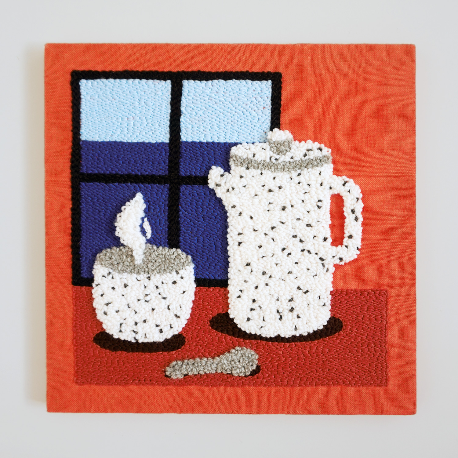 A fluffy punch needle wall art, featuring a ceramic tea set in front of a window.