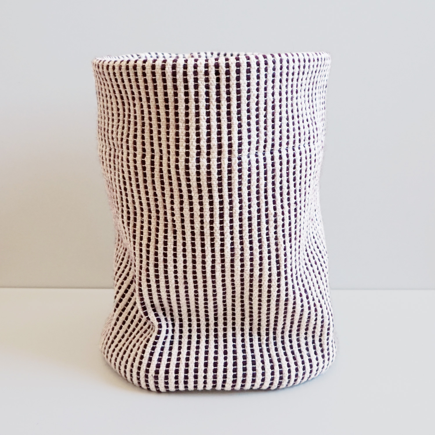 A sturdy beige and burgundy woven basket to hold your yarn stash, kid's toys or a big house plant.