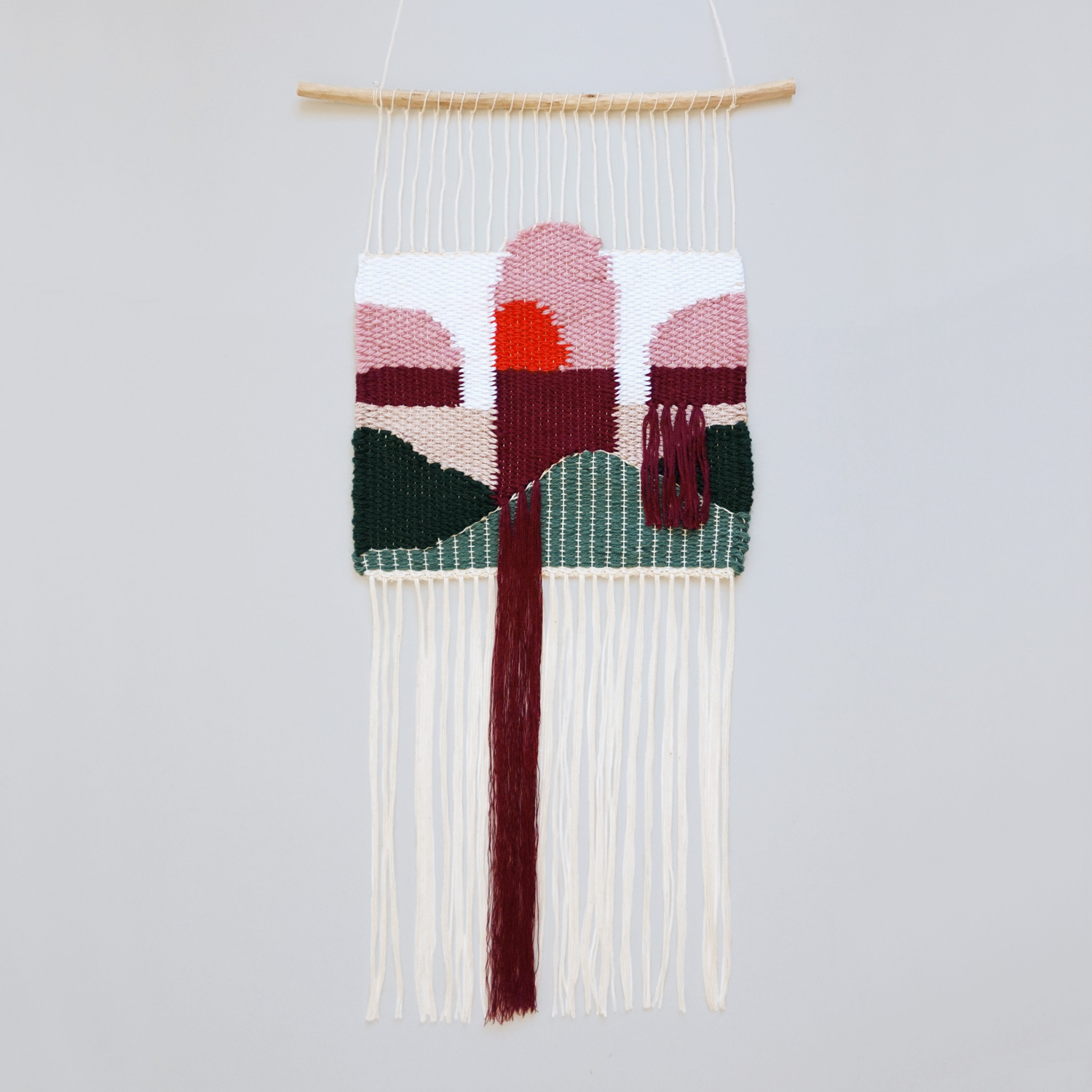 A woven mini wall hanging, featuring a serene scene with arches, waterfalls and a sunset.