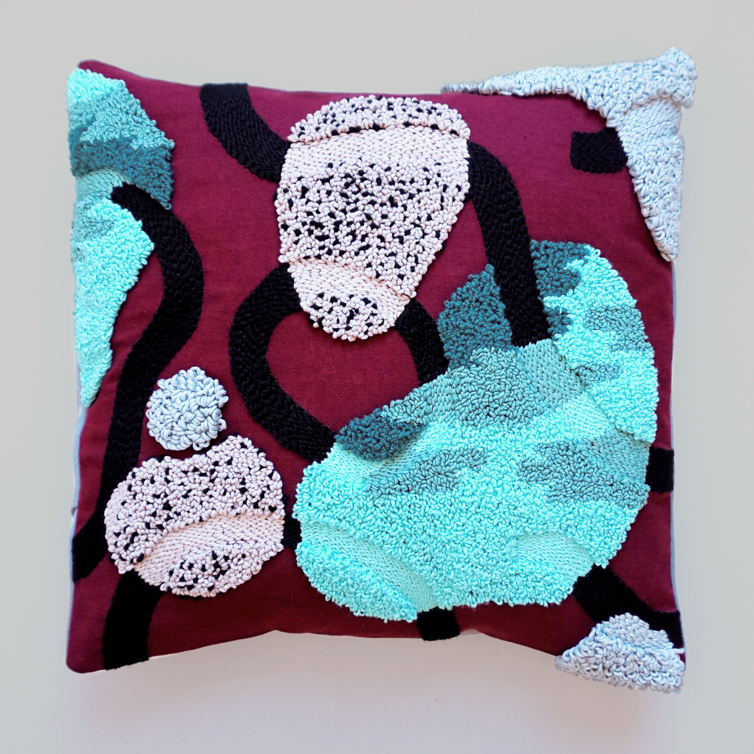 A flowy and fluffy punch needle pillow case, featuring a mossy river stone design.