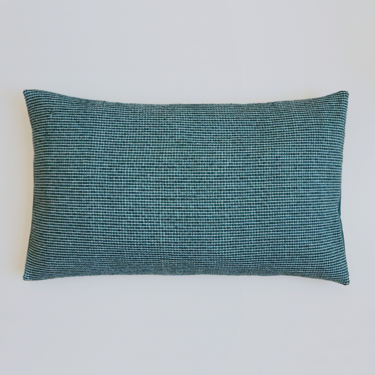 An extra large and extra soft deep green woven pillow, filled with a zero waste scrap insert.