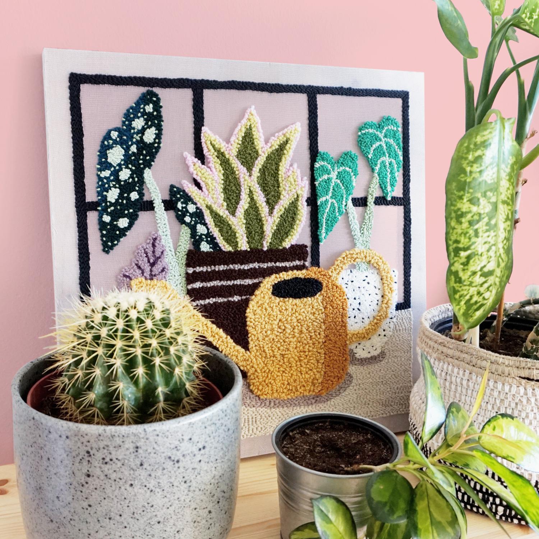A semi-transparent punch needle art work depicting a plant shelf inside a green house.