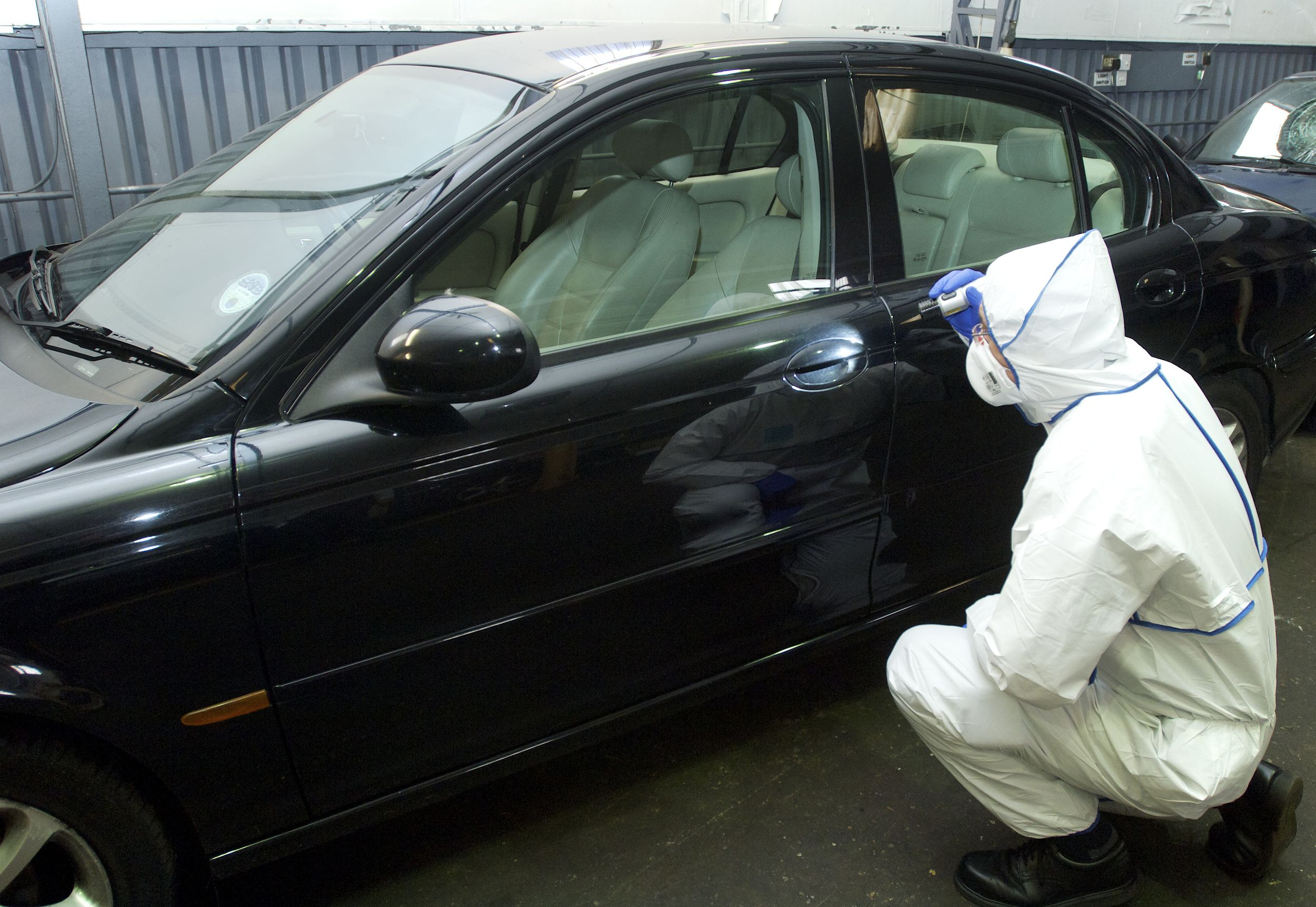 Image of a Police CSI examining a car for fingerprints
