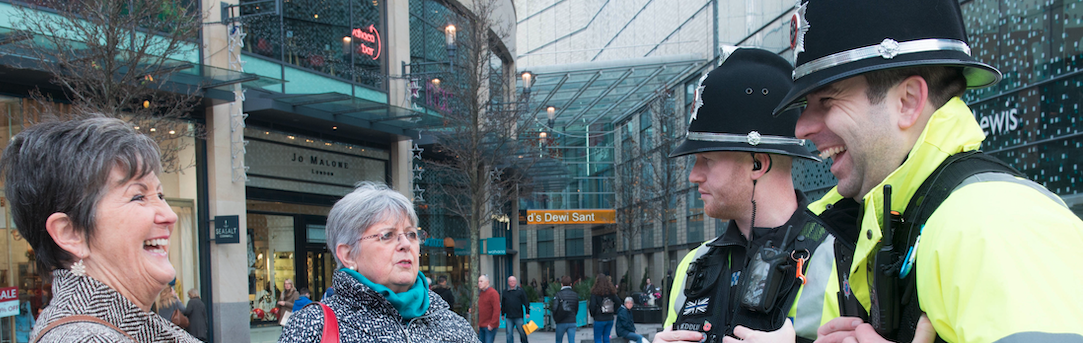 Stock Photo of two officers outside a shopping centre speaking to members of the public