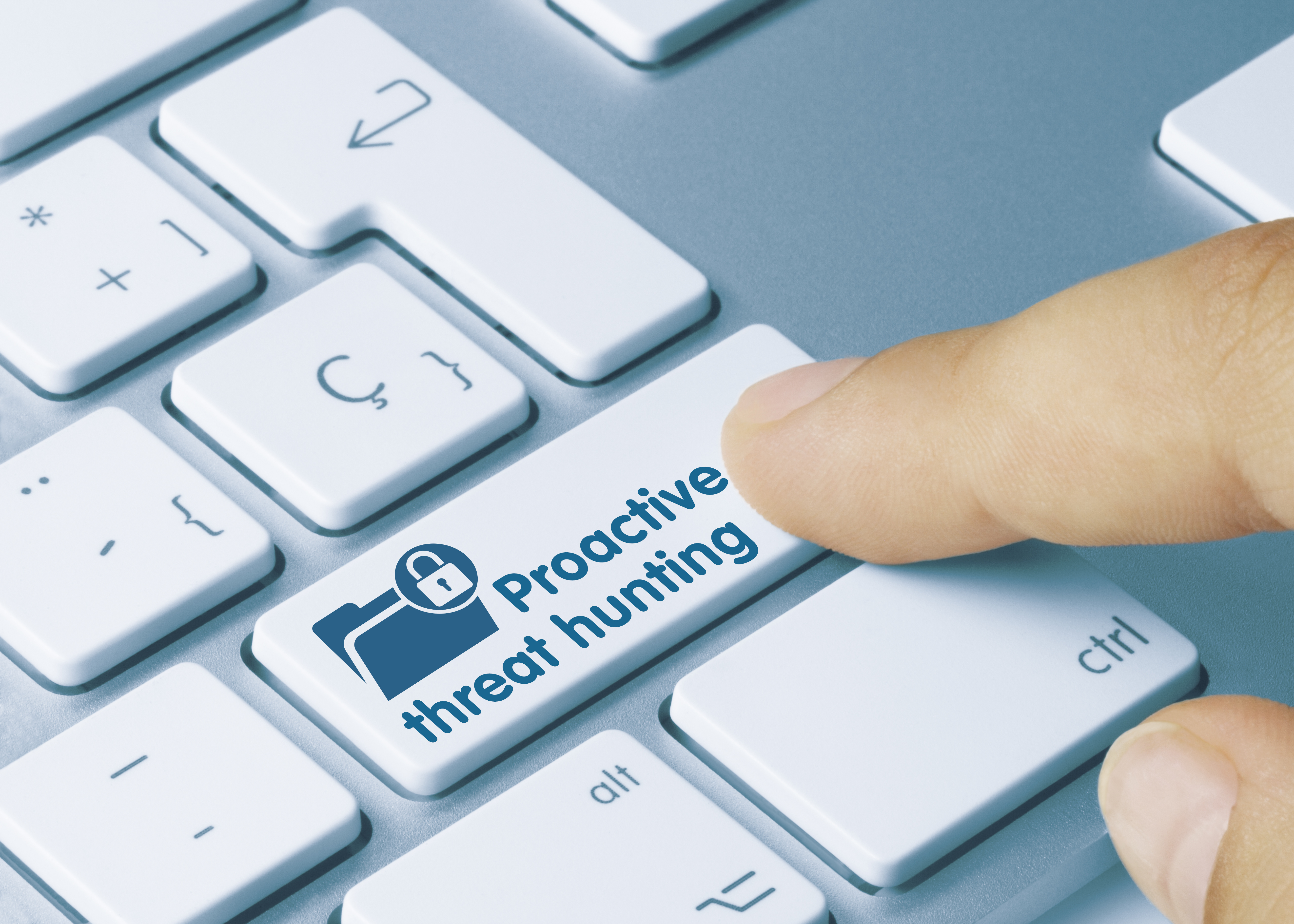 Stock photo of a finger pointing at a computer keyboard marked Proactive Threat Hunting