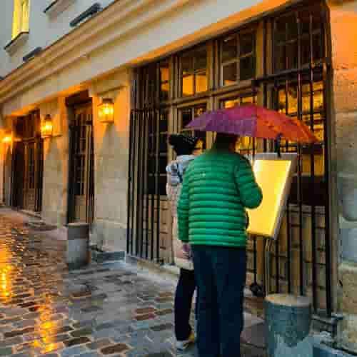 Deux passants regardent le menu extérieur sous la pluie.