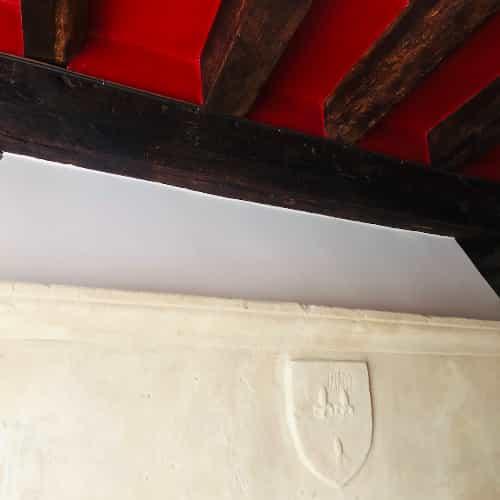 Contraste entre le rouge vif du plafond et la couleur claire de la pierre.