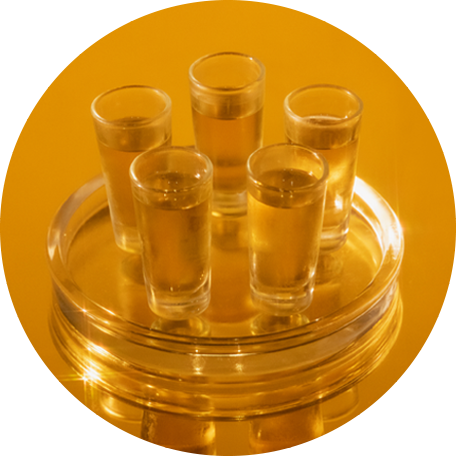Five bright shot glasses filled with Basbas