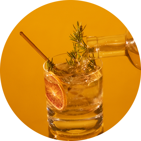 Cocktail made with tonic, an orange peel and fresh herbs