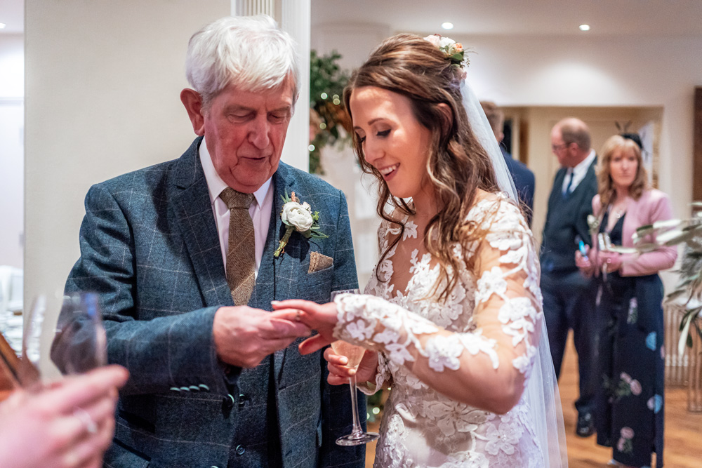 Bride and grandfather admiring the ring