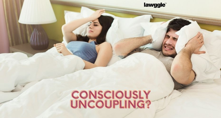 A couple lies in bed beside each other, each looking frustrated with the other.