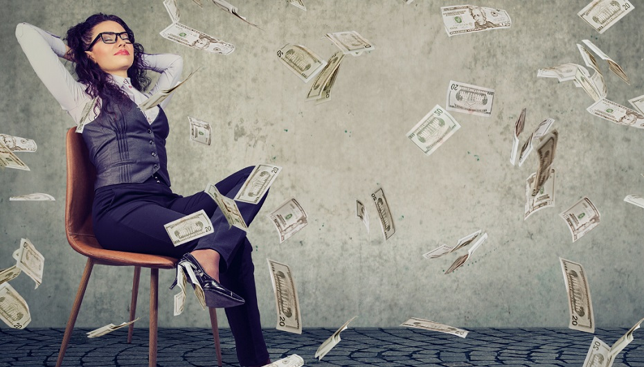 A contented looking woman leans back in a chair as paper money rains down around her.