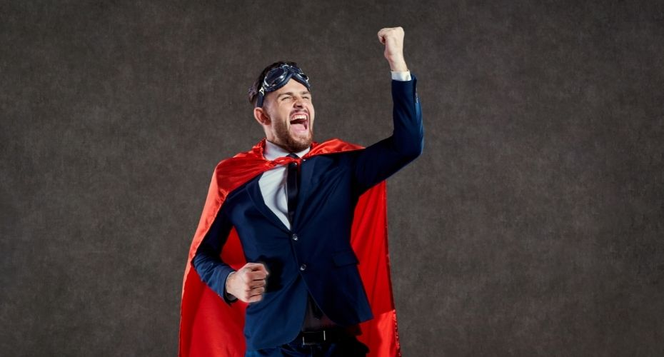 A lawyer wearing a suit, a superhero cape, and goggles raises their fist in the air in a successful cheer.